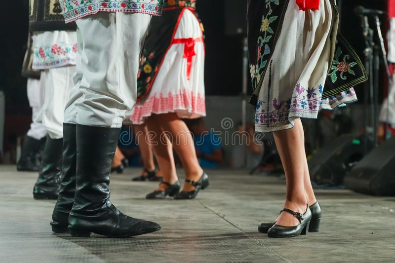 Close up of legs of young Romanian female and male dancers in traditional folkloric costume. Folklore of Romania stock photography