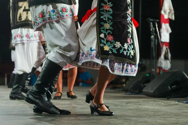 Close up of legs of young Romanian female and male dancers in traditional folkloric costume. Folklore of Romania stock photo