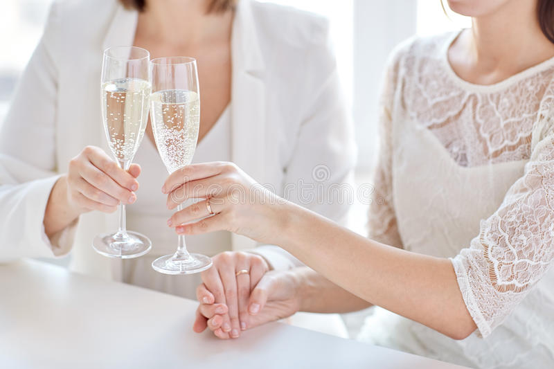 Close up of lesbian couple with champagne glasses. People, homosexuality, same-sex marriage, celebration and love concept - close up of happy married lesbian royalty free stock photo