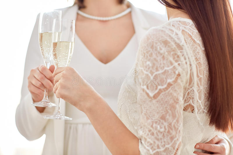 Close up of lesbian couple with champagne glasses. People, homosexuality, same-sex marriage, celebration and love concept - close up of happy married lesbian royalty free stock photos