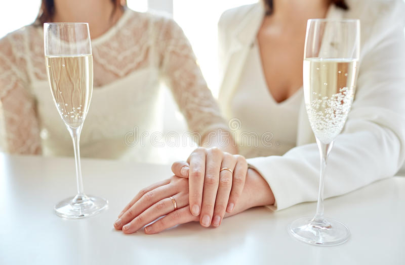 Close up of lesbian couple with champagne glasses. People, homosexuality, same-sex marriage, celebration and love concept - close up of happy married lesbian royalty free stock image