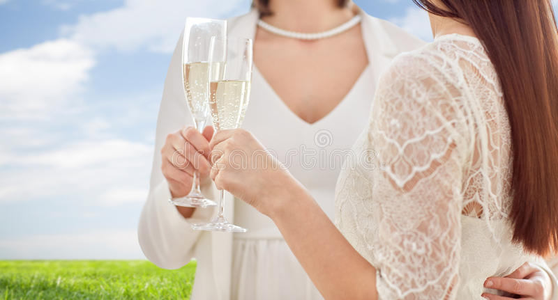 Close up of lesbian couple with champagne glasses. People, homosexuality, same-sex marriage, celebration and love concept - close up of happy married lesbian stock photo