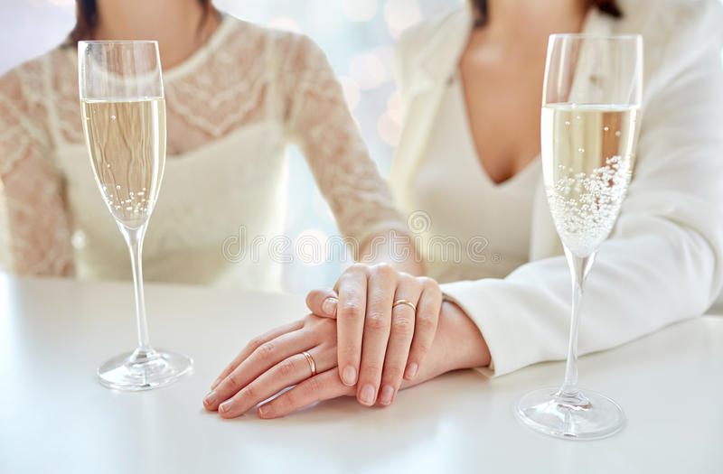 Close up of lesbian couple with champagne glasses. People, homosexuality, same-sex marriage, celebration and love concept - close up of happy married lesbian stock image