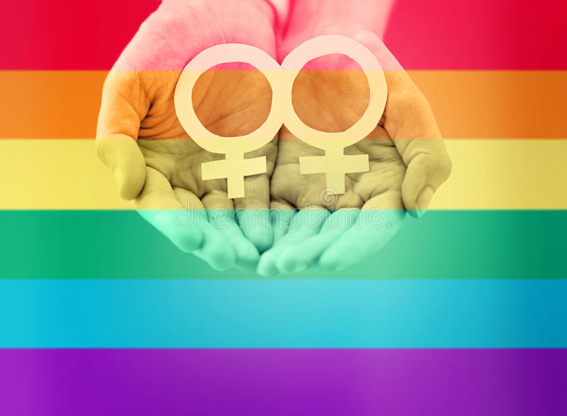 Close up of lesbian couple hands with venus symbol. People, homosexuality, same-sex marriage, gay pride and love concept - close up of happy lesbian couple hands royalty free stock images