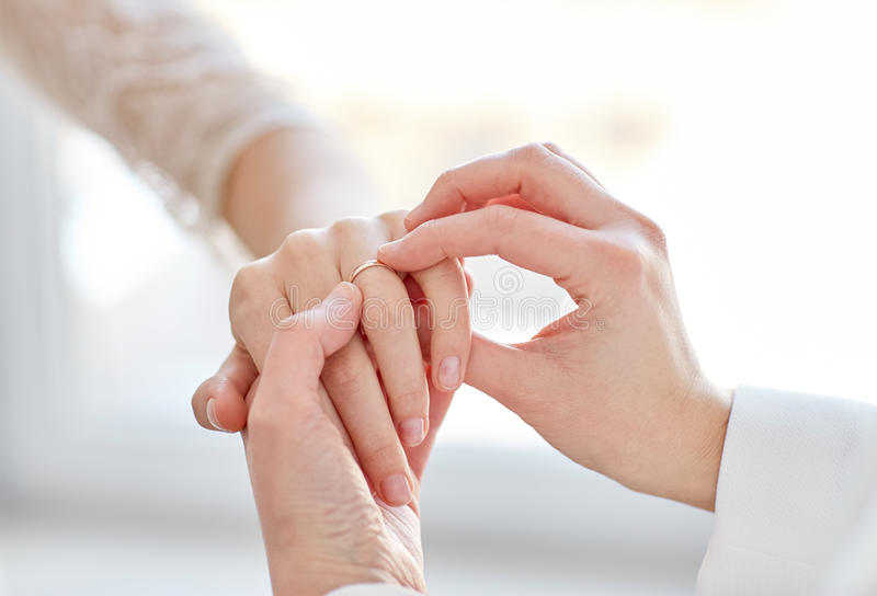 Close up of lesbian couple hands with wedding ring. People, homosexuality, same-sex marriage and love concept - close up of happy lesbian couple hands putting on stock photos