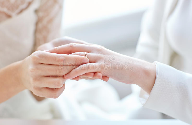 Close up of lesbian couple hands with wedding ring. People, homosexuality, same-sex marriage and love concept - close up of happy lesbian couple hands putting on royalty free stock photos