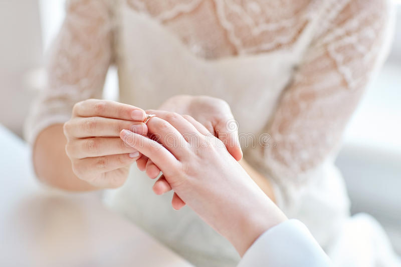 Close up of lesbian couple hands with wedding ring. People, homosexuality, same-sex marriage and love concept - close up of happy lesbian couple hands putting on stock images