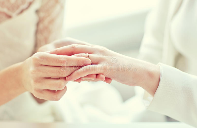 Close up of lesbian couple hands with wedding ring. People, homosexuality, same-sex marriage and love concept - close up of happy lesbian couple hands putting on stock image