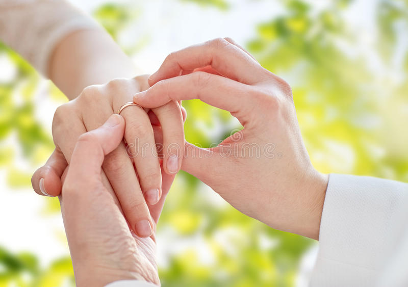 Close up of lesbian couple hands with wedding ring. People, homosexuality, same-sex marriage, summer and love concept - close up of happy lesbian couple hands royalty free stock images