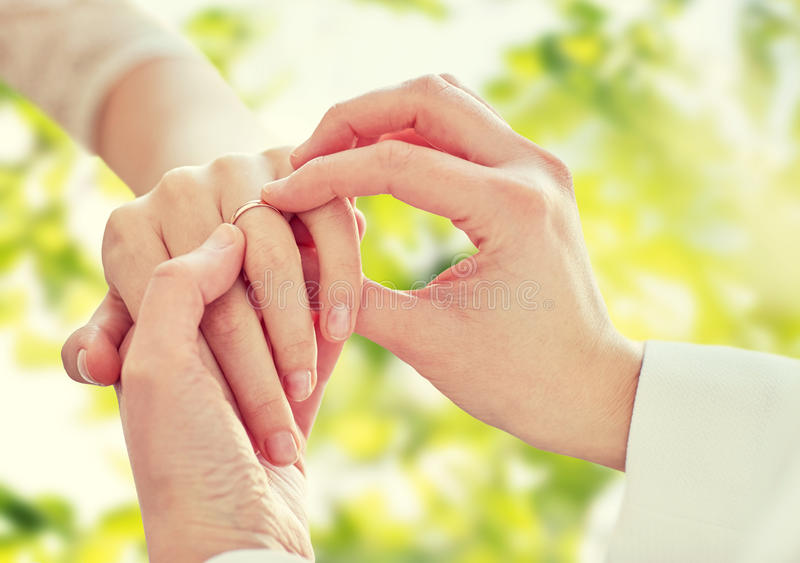 Close up of lesbian couple hands with wedding ring. People, homosexuality, same-sex marriage, summer and love concept - close up of happy lesbian couple hands royalty free stock photo