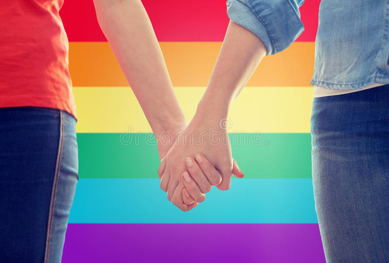 Close up of lesbian couple holding hands. People, homosexuality, same-sex marriage, gay and love concept - close up of happy lesbian couple holding hands over royalty free stock images