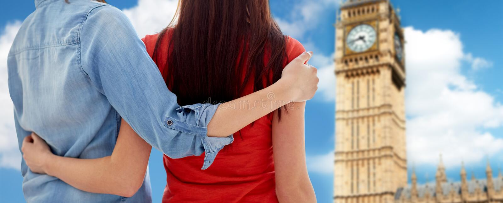 Close up of lesbian couple hugging over big ben. People, homosexuality, same-sex marriage, travel and gay love concept - close up of happy women couple hugging royalty free stock image
