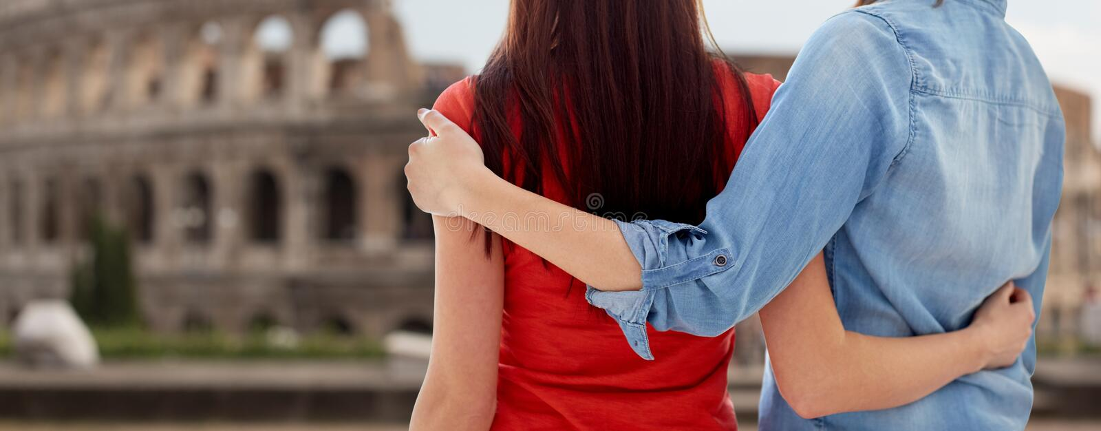 Close up of lesbian couple over coliseum in rome. People, homosexuality, same-sex marriage, travel and gay love concept - close up of happy lesbian couple stock photography