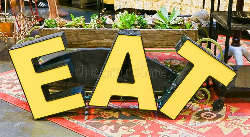 A Large Eat sign. A close up of the letters EAT in yellow and black royalty free stock photos