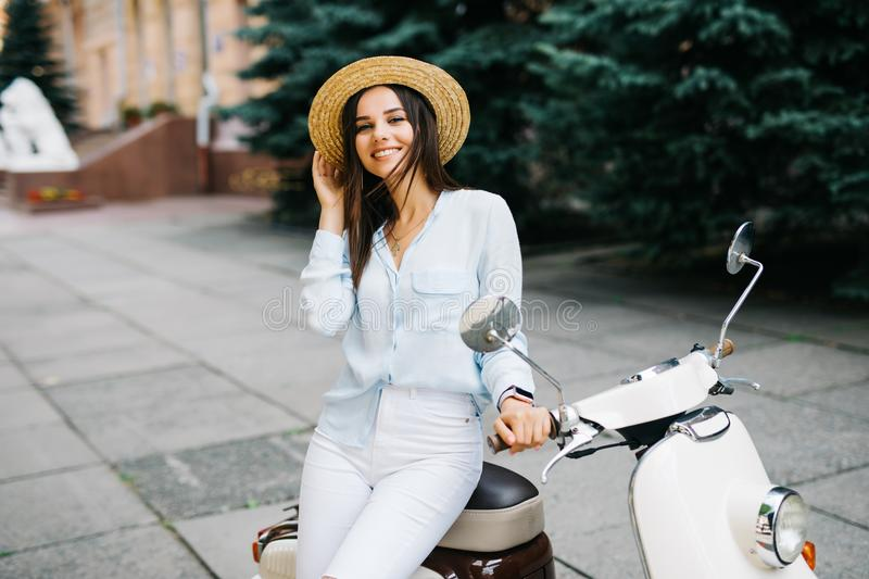 Close up lifestyle image of young fashionable woman in casual outfit sitting on scooter on the street. Wearing blue shirt, white p stock photo
