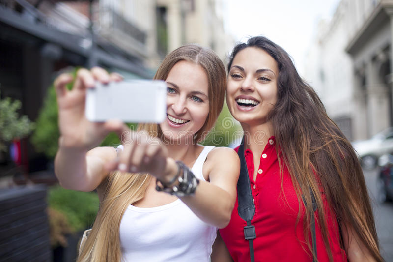 Close up lifestyle portrait of girls best friends makes funny gr stock photos