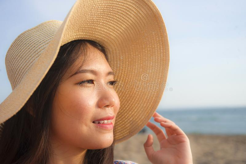 Close up lifestyle portrait of young beautiful and happy Asian Chinese tourist woman in Summer hat smiling cheerful at tropical is stock photography