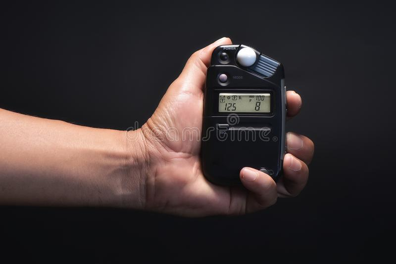 Close up light meter in hand. Light meter working in hand royalty free stock photo