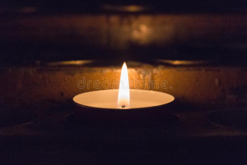 Close up of lighted tealight candle. Burning candle. The close up view of lighted tealight candle stock images