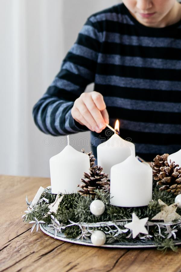 Close up of lighting the first candle on Advent Wreath. On the first Sunday in December. Celebrating Christmas holidays, swiss tradition stock photo