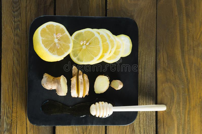 Lime, garlic and honey dipper in black slate plate. Close-up of lime, garlic and honey dipper in black slate plate royalty free stock photo