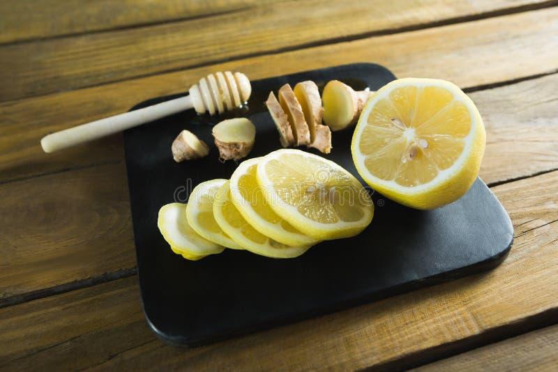 Lime, garlic and honey dipper in black slate plate. Close-up of lime, garlic and honey dipper in black slate plate stock photos