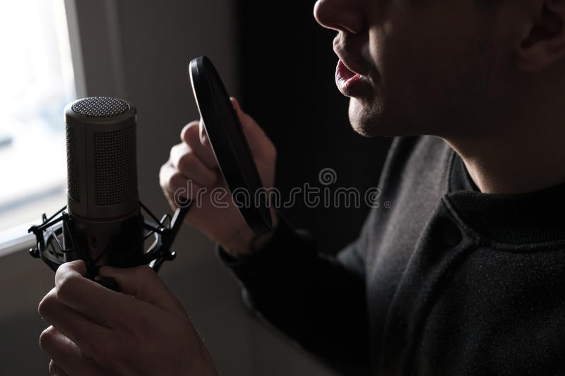 A close-up of lips at the microphone of a singing young man standing. In profile, horizontal photo royalty free stock images