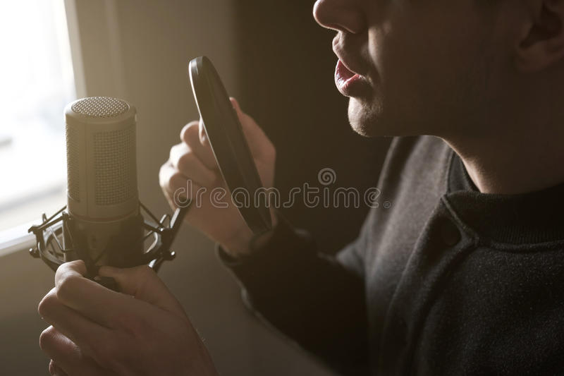 A close-up of lips at the microphone of a singing young man standing in profile in the rays of the sun. Horizontal photo stock photography