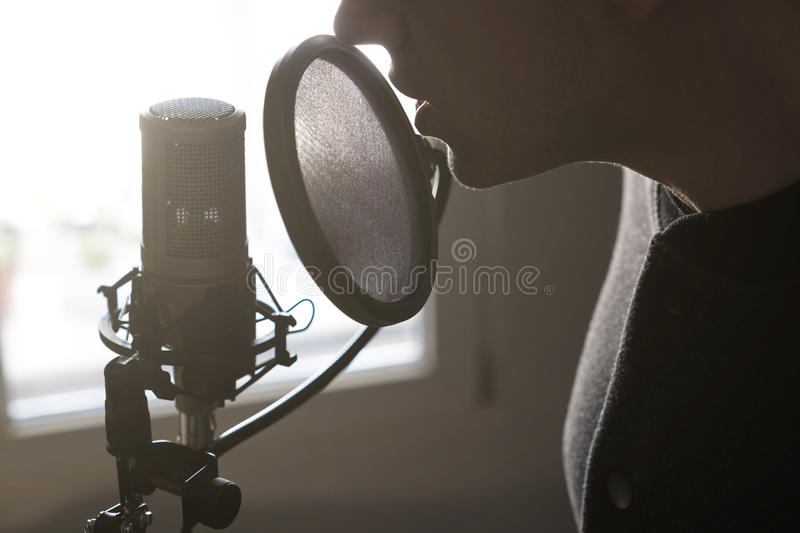 A close-up of lips at the microphone of a young man standing in profile in the rays of the sun. Horizontal photo royalty free stock photos