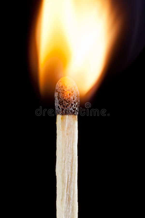 Close-up lit match with flame on black background stock photos
