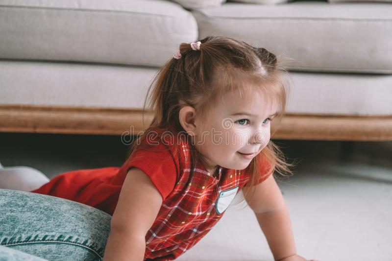 Close up little adorable thoughtful girl dreaming lying on a floor in a living room at modern home stock image