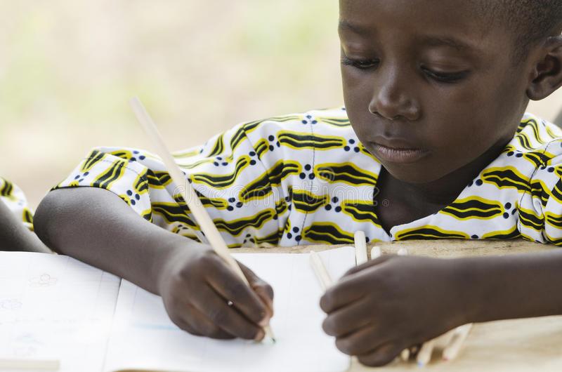 Close-up of little African boy studying and drawing stock photo