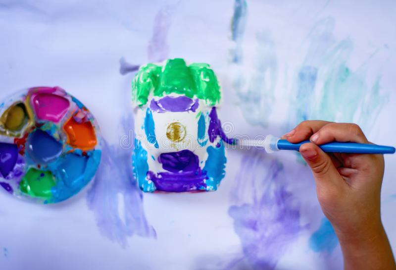 Little asian child girl right hands painting color on the plaster car statue with bright blue paintbrush and colorful watercolor royalty free stock image