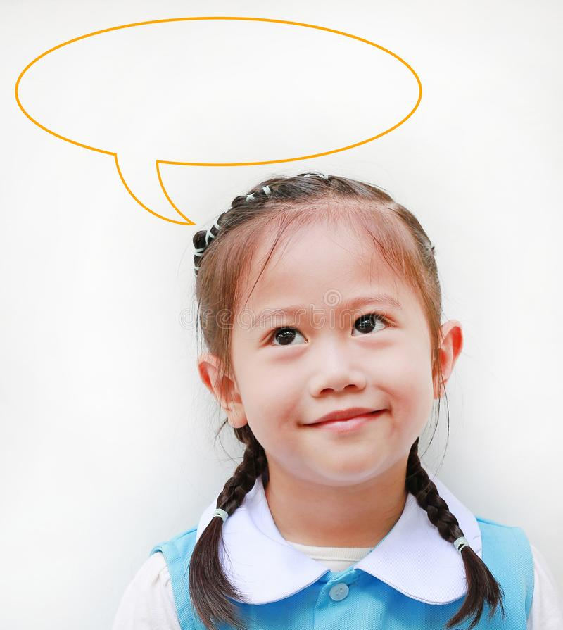Close up little Asian girl in school uniform looking up and speak bubble thinking something. Imagination concept.  royalty free stock image