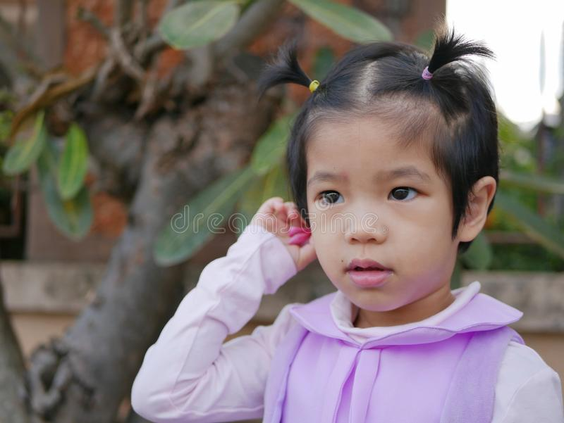 Close up of little Asian, Thai, baby girl, putting a flower behind her ear stock images
