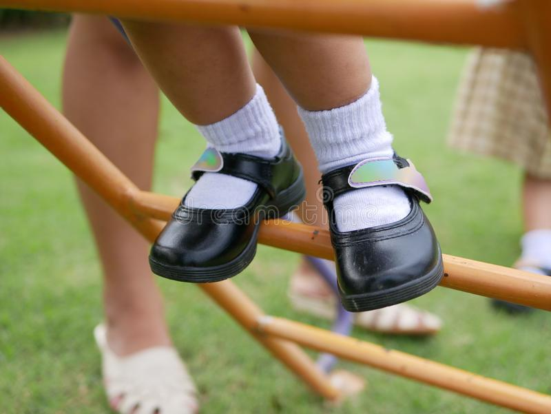 Close up of little baby`s feet standing on a metallic stairs at a playground learning to climb it up. Large muscle and motor development in baby through royalty free stock photos