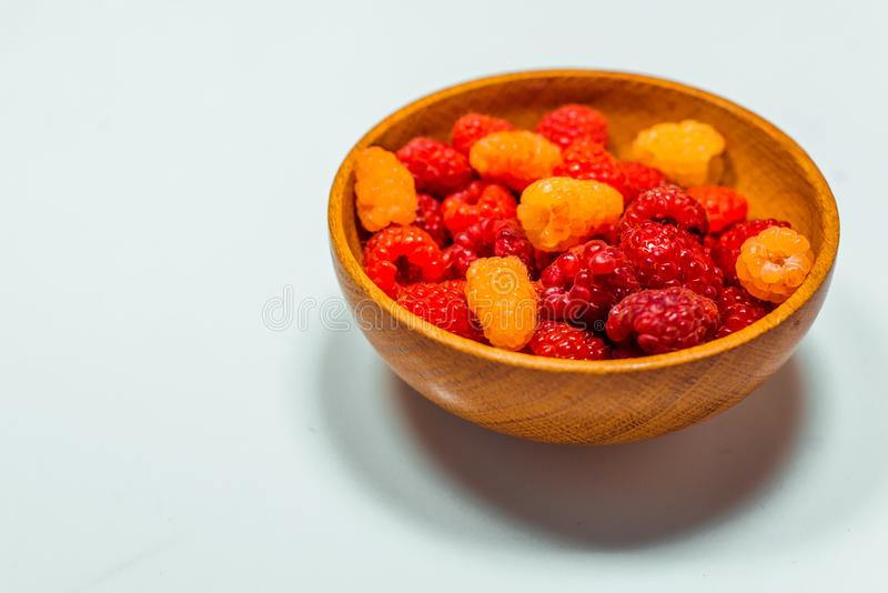 Close up little basket with red and yellow raspberries on white royalty free stock photos