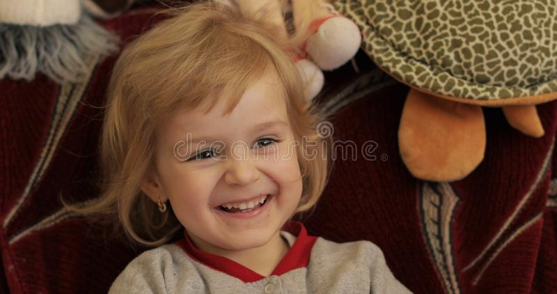 Close up of a little blonde cute girl face. Girl smiling. Inside. Portrait shot stock photos