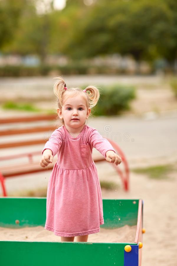 Little girl in a pink dress in a sandbox. royalty free stock photos