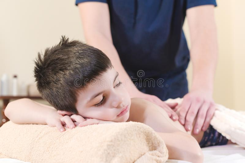 Close up A little boy relaxes from a therapeutic massage. Male massage therapist makes a medical massage to the back of stock photography