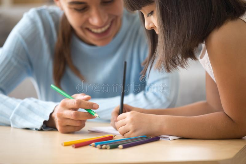 Close up little child drawing with mother royalty free stock photography
