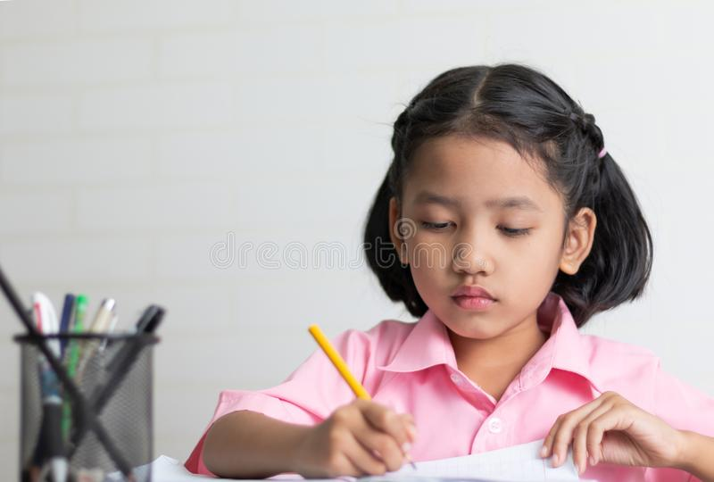 Close up the little girl is doing homework intently stock photography
