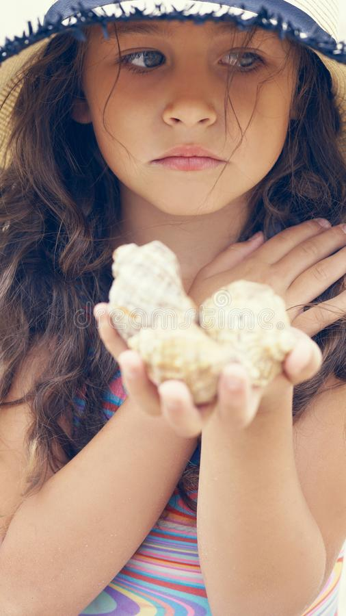 Close up of sad little girl in hat holding sea shells in her hands. royalty free stock photos
