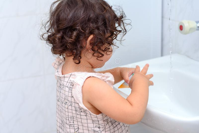 Little cute baby girl cleaning her teeth with toothbrush in the bathroom. stock image