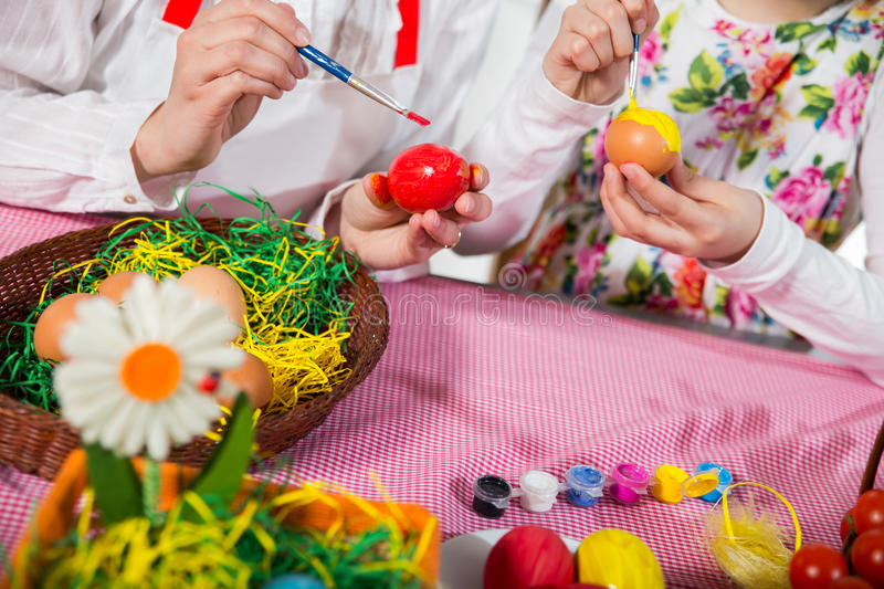 Close up of little girl and mother coloring eggs for Easter royalty free stock photo