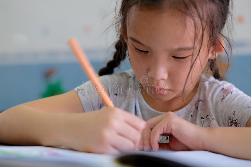 Close up of little girl is painting on paper, Write on the book  intently stock photos