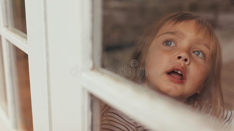 Little girl sitting by the window royalty free stock images