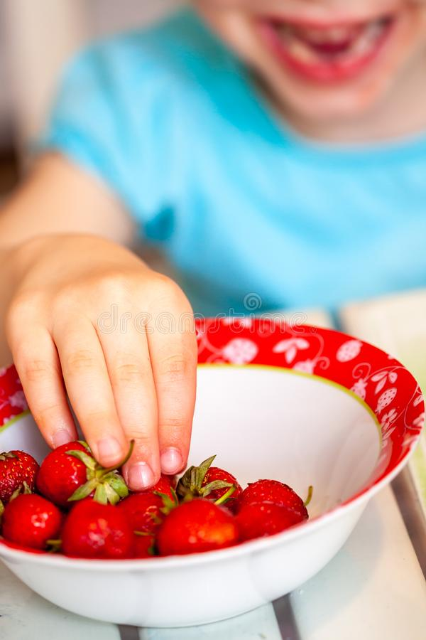 Close up of little girl taking from strawberry bowl royalty free stock image