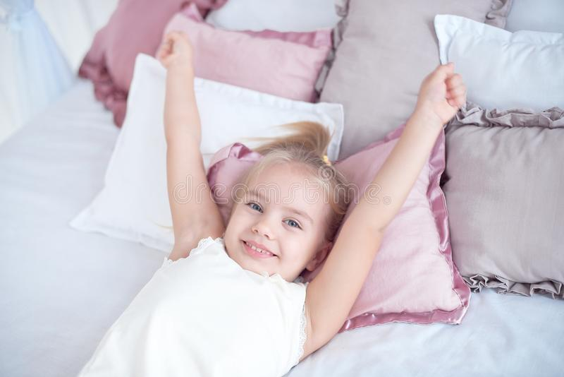 Close-up little girl waking up with stretching arms while awake lying on white bed linen stock photo