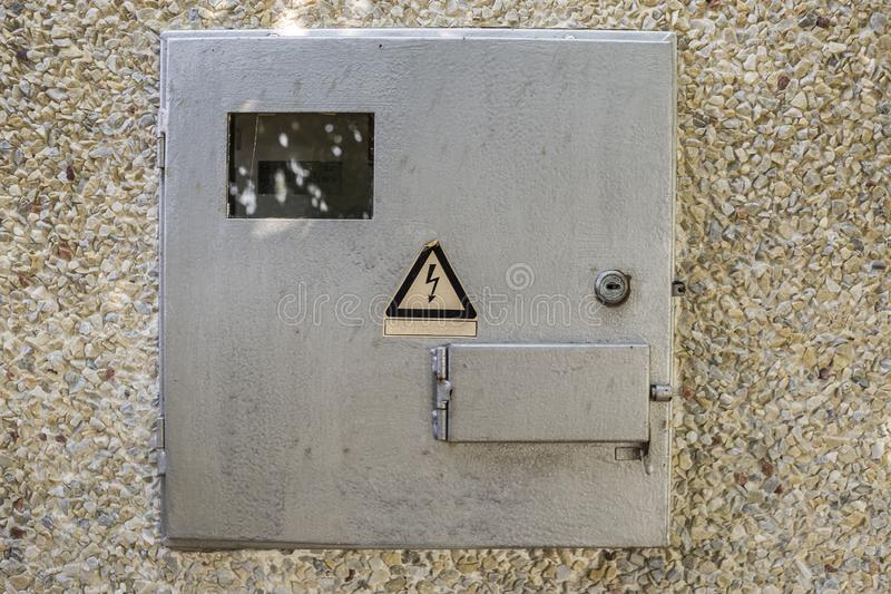 Close-up of locked electrical metal light blue meter box with warning caution sign outside on exterior house wall. Measurement stock photography
